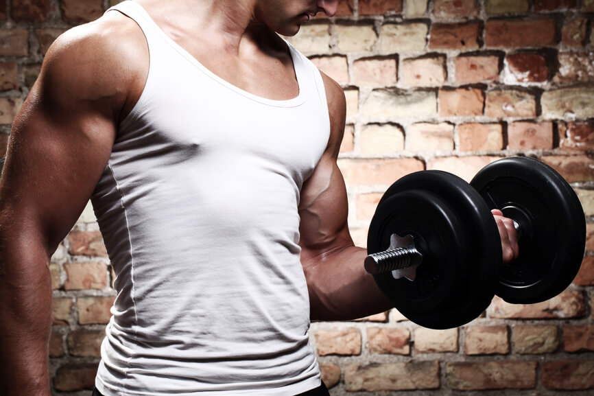 Muscular guy doing exercises with dumbbell against a brick wall